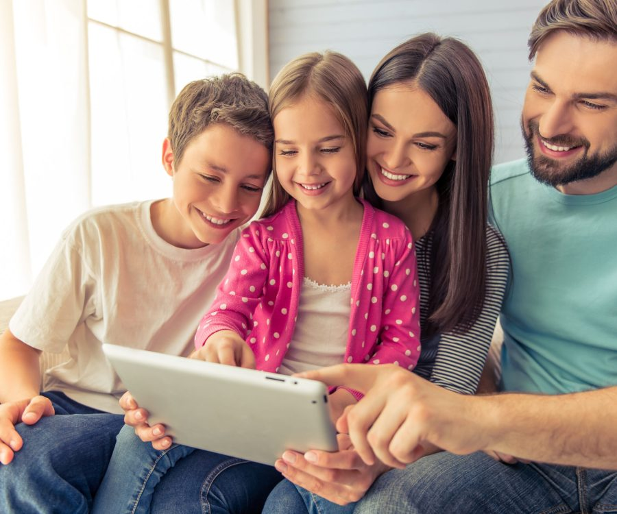 Beautiful young parents, their cute little daughter and son are using a tablet and smiling, sitting on sofa at home
